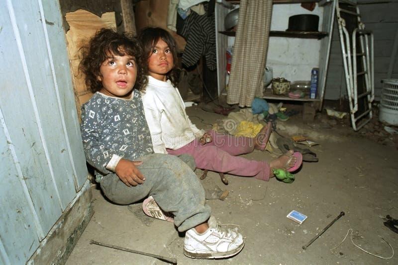 Arme argentinische Mädchen des Porträts, die in der Elendsviertelwohnung spielen lizenzfreie stockfotos