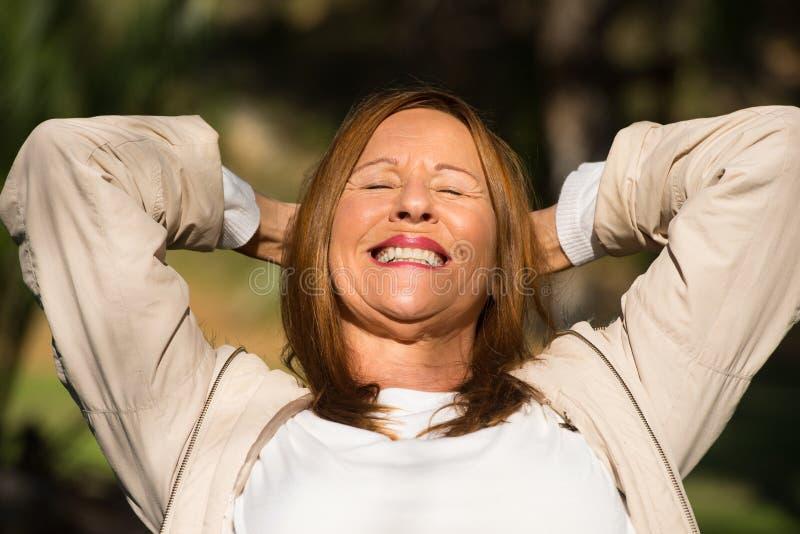 Arme der frohen entspannten Frau im Freien oben stockfotografie