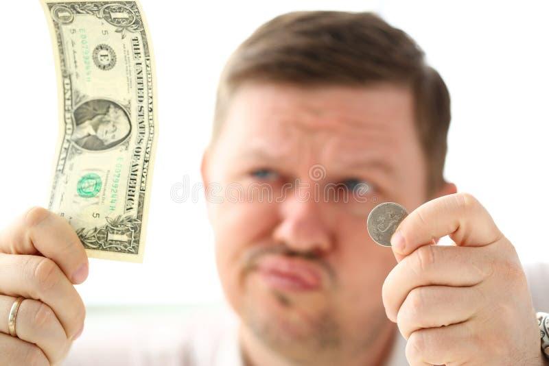 Arme des durchdachten Mannes Papier- und Münzenwährung halten lizenzfreie stockbilder