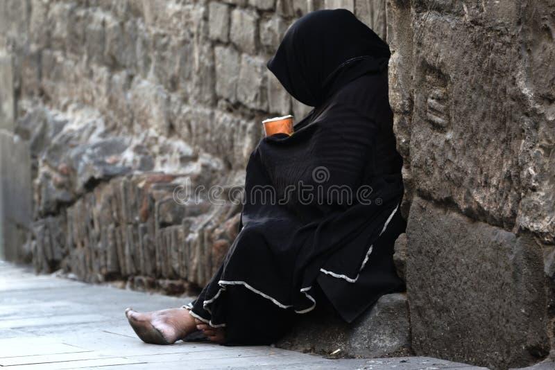 Arme, die das Sitzen in der Straße bitten stockbilder