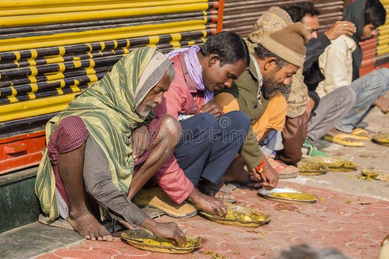 Arme indische Leute, die freies Lebensmittel an der Straße in Varanasi, Indien essen lizenzfreie stockbilder