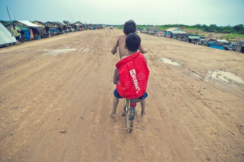 Arme kambodschanische Kinder, die mit altem Fahrrad laufen stockfoto