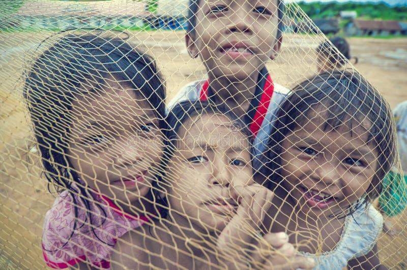 Arme kambodschanische Kinder, die mit Schleppnetz spielen stockfotos