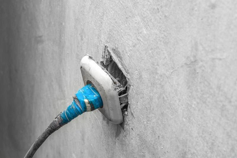 Arme oude elektricien in de reparatie van de elektrische outlet van het gebouw royalty-vrije stock afbeeldingen