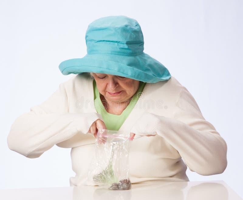 Arme reife Frau betrachtet in der Tasche Münzen stockfoto