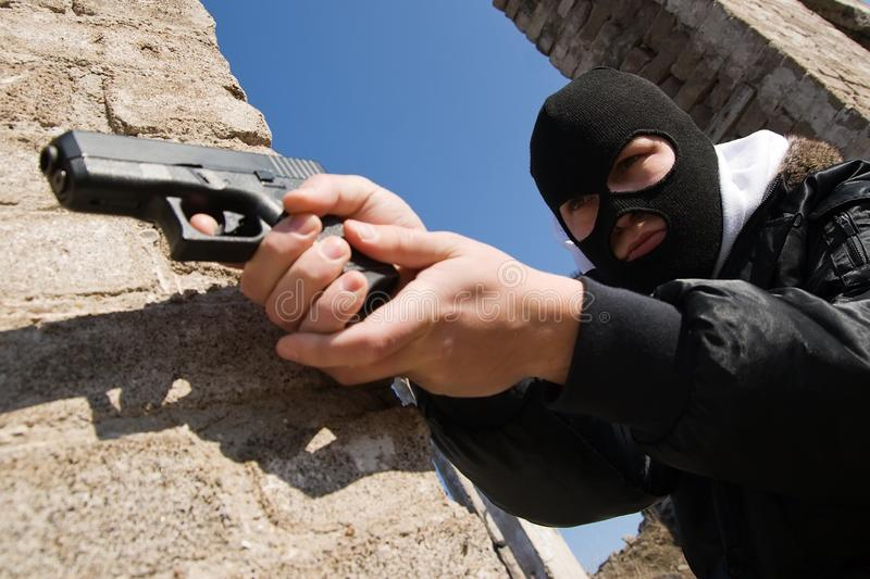 Armed criminal aiming with a pistol royalty free stock images