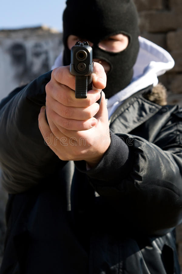 Armed criminal aiming you. Criminal with a gun aiming his target royalty free stock images