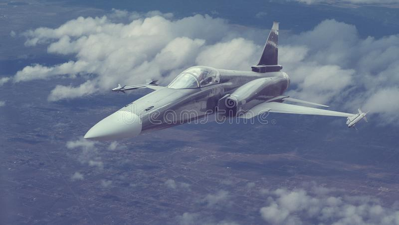 A fighter jet flying at a high altitude over big city or populated area royalty free stock image