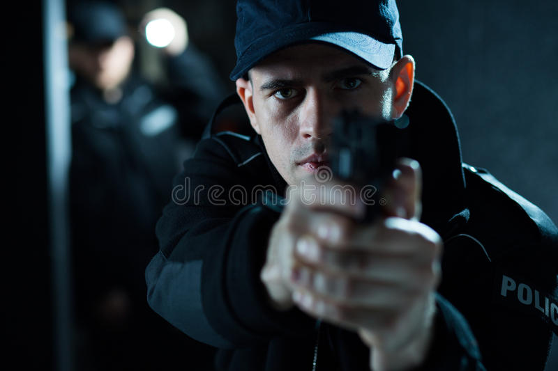 Armed male pointing pistol. Close up of an armed policeman pointing pistol royalty free stock photography