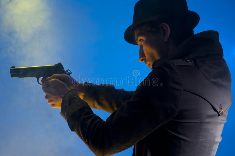 Armed Man. Man holding a gun, shooted in studio on a blue background with yellow light and smoke royalty free stock photo