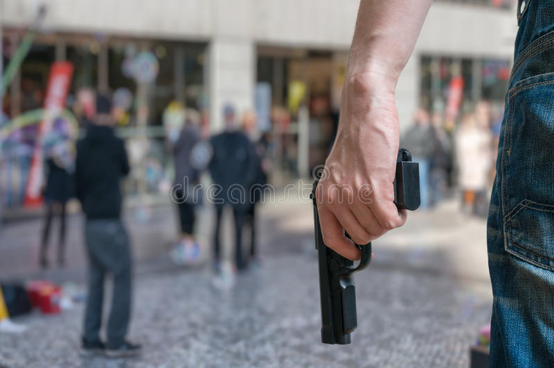 Armed man (attacker) holds pistol in public place. Many people on street. Gun control concept royalty free stock photos