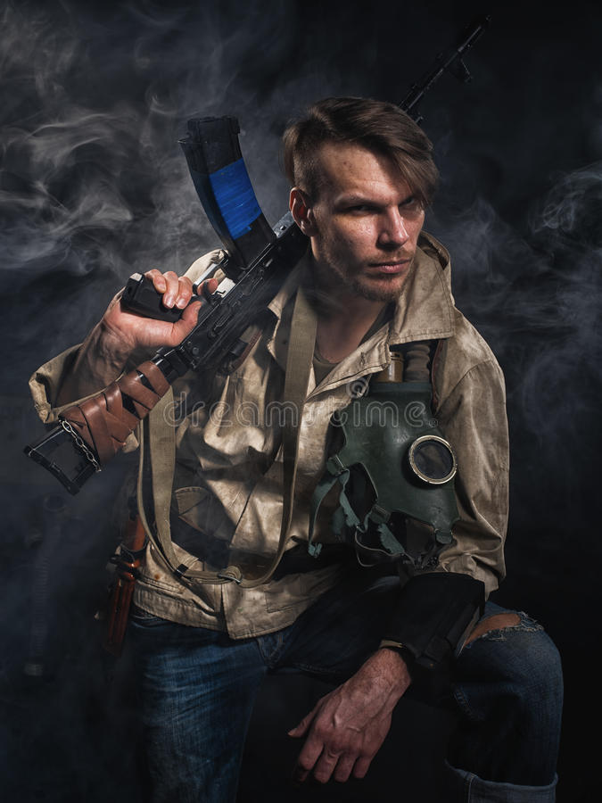 Armed man with a gun. Stalker. Armed man with a gun. Post-apocalyptic fiction. Stalker stock photography