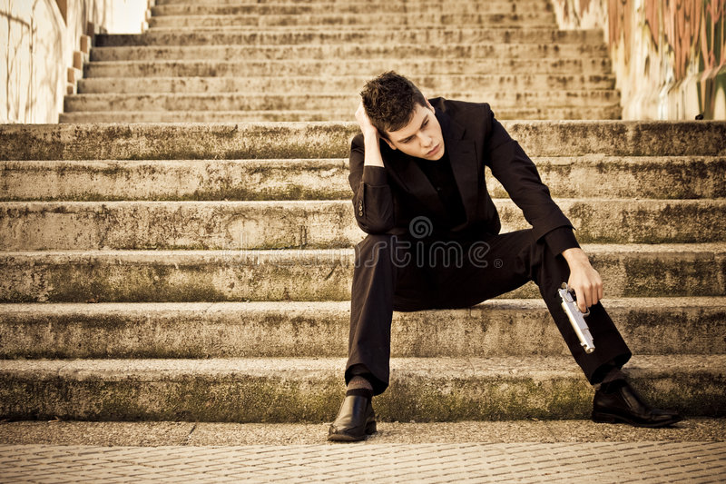 Armed man in stairs. Young armed man waiting on the steps stock photos