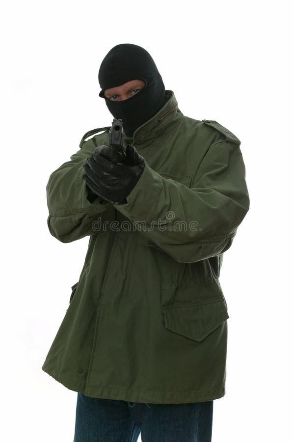 Armed militia. Armed man in a balaclava aiming a handgun at his target royalty free stock photos