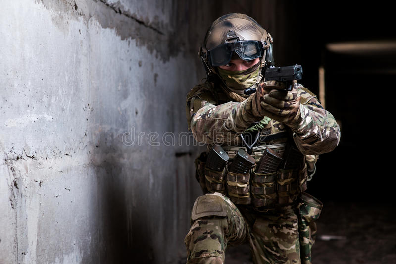 Armed ranger in camouflage aiming his gun in the dark room royalty free stock photos