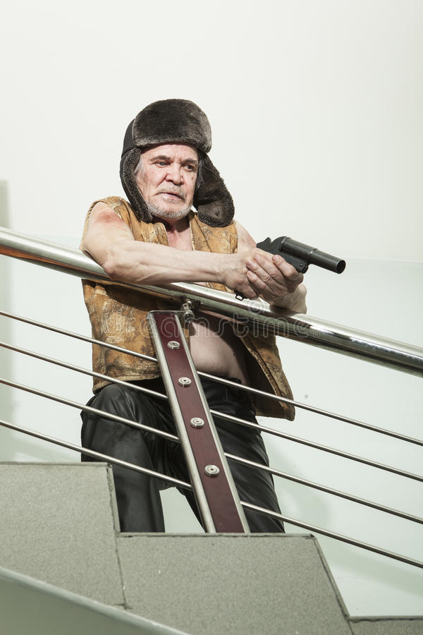 Armed robber with a gun on the emergency stairs. Bandit armed with a gun waiting for a victim at the site of the emergency stairs royalty free stock photos