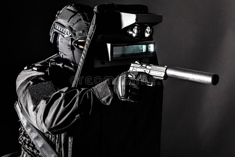 Armed SWAT fighter hiding behind ballistic shield. Police special forces fighter, assault team member, tactical group officer in black uniforms, aiming with stock photography