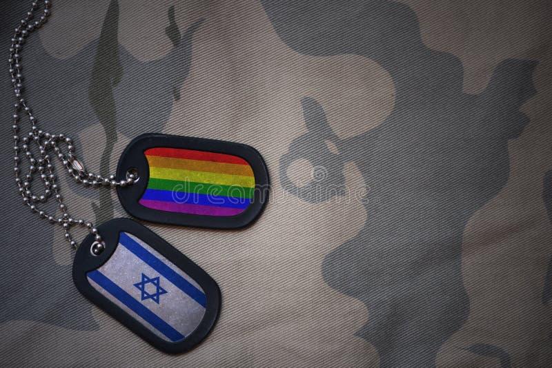 Armeefreier raum, Erkennungsmarke mit Flagge von Israel und homosexueller Regenbogenflagge auf dem kakifarbigen Beschaffenheitshi lizenzfreie abbildung