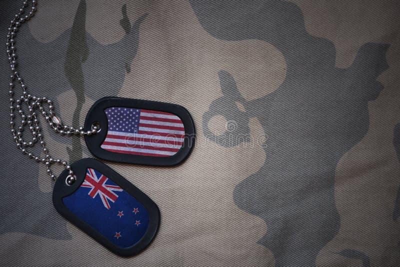 Armeefreier raum, Erkennungsmarke mit Flagge von Staaten von Amerika und Neuseeland auf dem kakifarbigen Beschaffenheitshintergru stockfoto