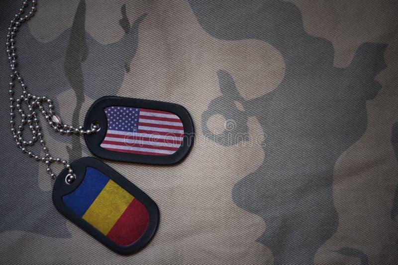 Armeefreier raum, Erkennungsmarke mit Flagge von Staaten von Amerika und Rumänien auf dem kakifarbigen Beschaffenheitshintergrund stockfotos