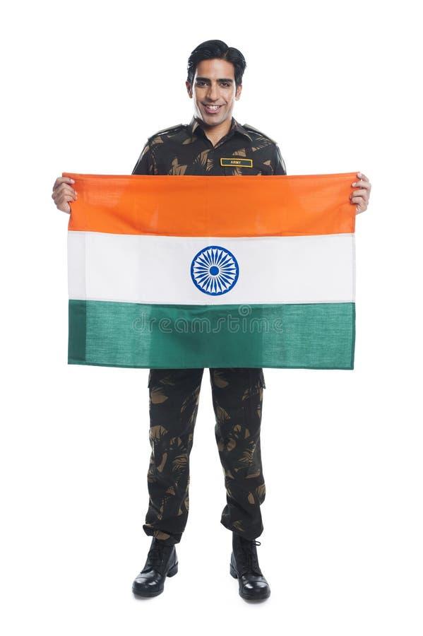 Armeesoldat, der indische Flagge und das Lächeln hält lizenzfreies stockfoto