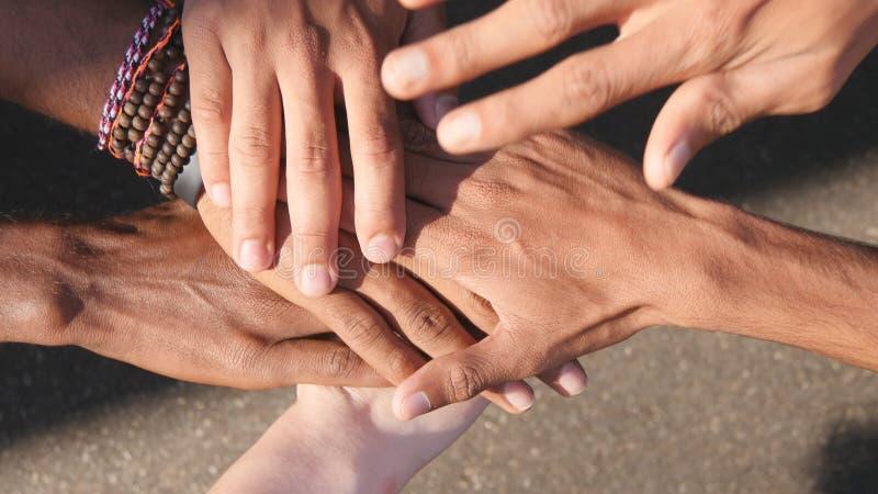 Armen springer allra och färger som tillsammans en och en staplas i enhet och teamwork och lyfts därefter Många blandras- händer arkivfoton