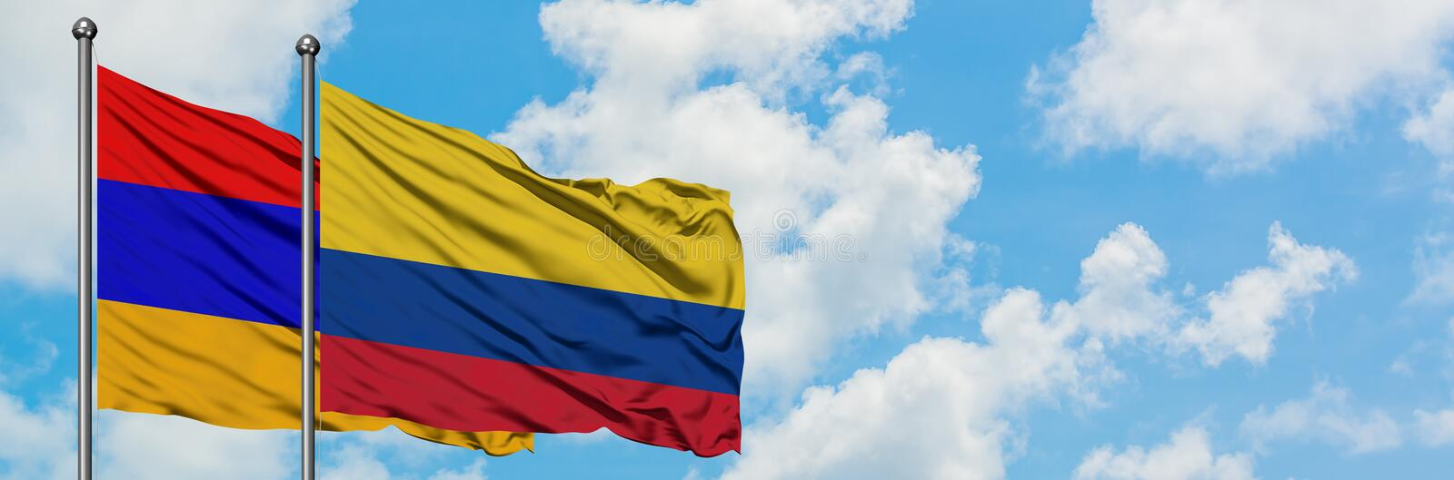 Armenia and Colombia flag waving in the wind against white cloudy blue sky together. Diplomacy concept, international relations. Peace, agreement, anthem stock image