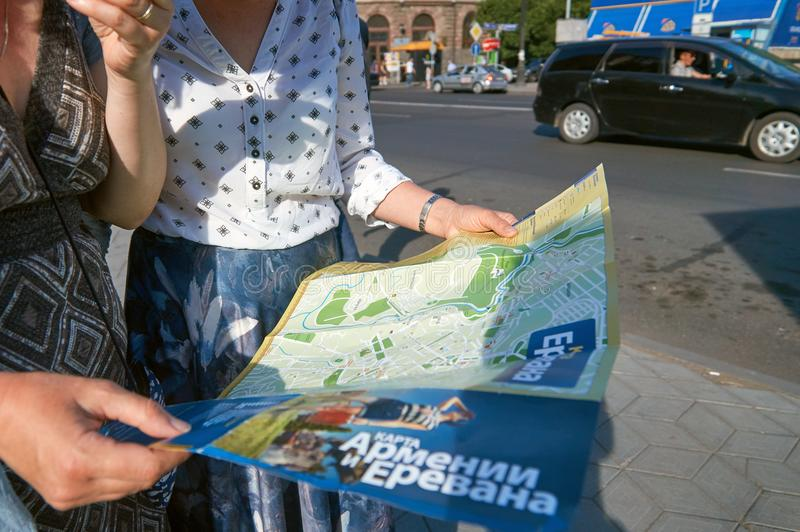 Armenia, Yerevan - June 12, 2017. Russian female tourists using a paper map on Yerevan street stock photography