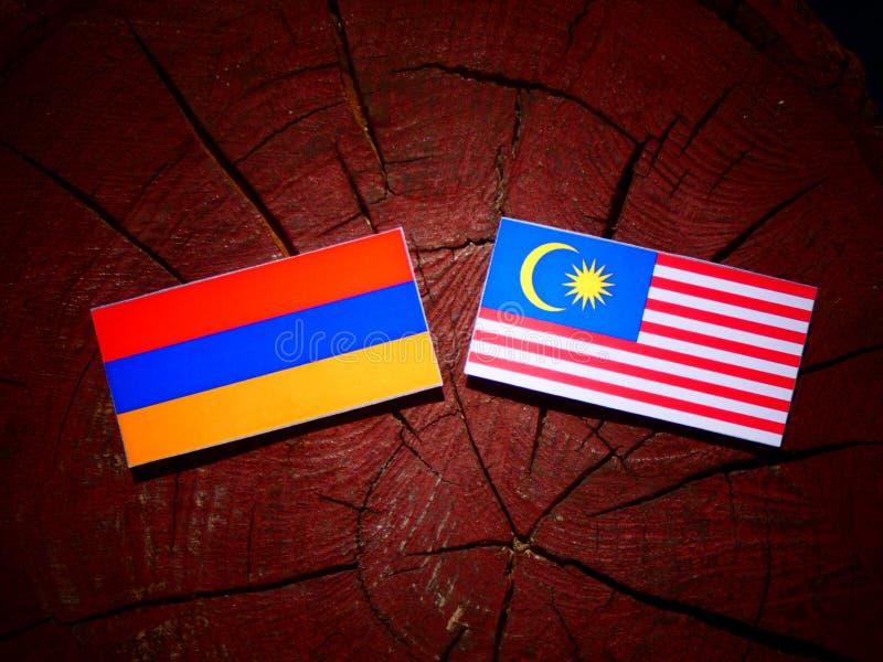 Armenian flag with Malaysian flag on a tree stump isolated vector illustration