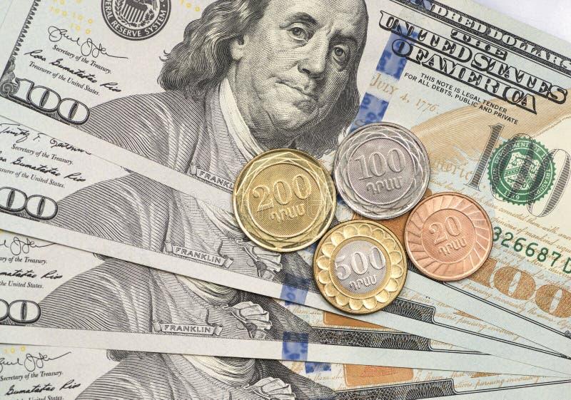 Armenische Drammünze auf Dollarscheine stockbilder