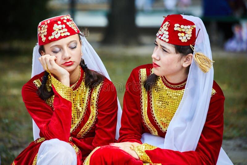 Armeniska Tatar flickor i folkloredräkter väntar på deras kapacitet arkivbilder