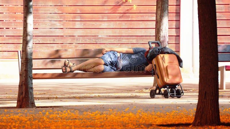 Armer Mann, der auf einer Bank in einem Park schläft Obdachloses und Sozialproblemkonzept leerer Kopienraum lizenzfreie stockfotografie