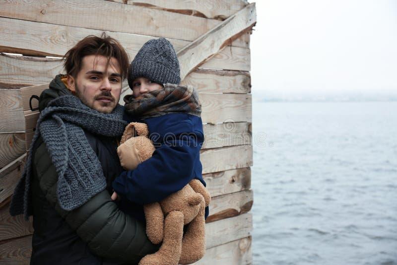 Armer Vater und Kind am Flussufer stockbild