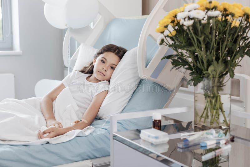 Armes Kind mit dem TropfenGegenlügen auf Krankenhausbett lizenzfreie stockbilder