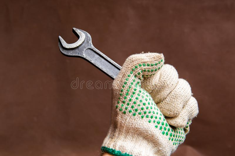 Armful of rusty wrench spanner in hand wearing protective glove stock images