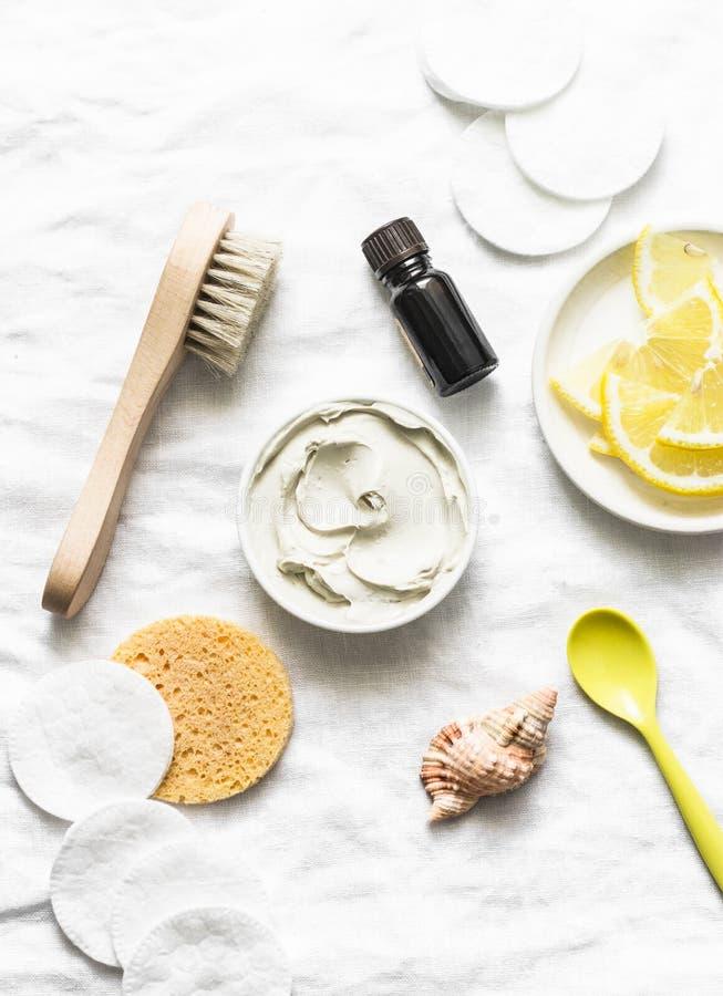 Armhåladetoxmaskering med vit lera, nödvändig olja för teträd och citronen på en ljus bakgrund arkivfoto