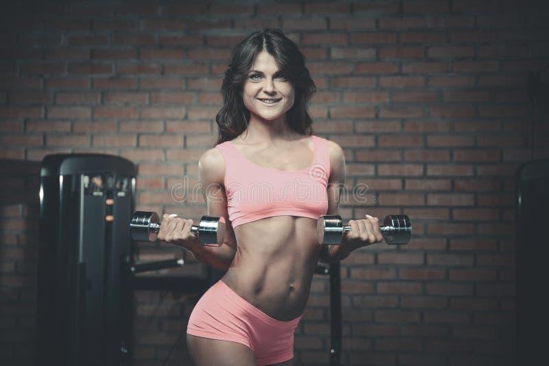 Armi atletiche sexy di addestramento della ragazza in palestra fotografia stock libera da diritti