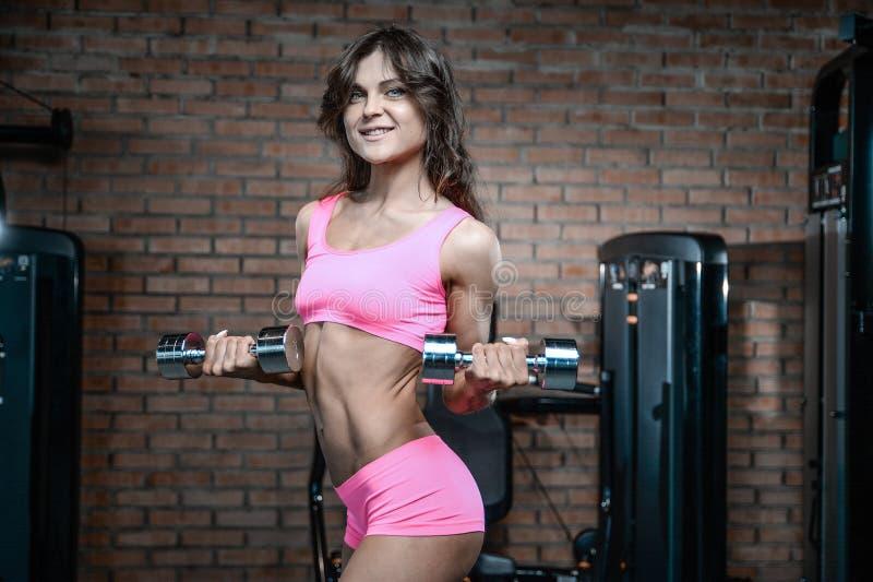 Armi atletiche sexy di addestramento della ragazza in palestra immagini stock