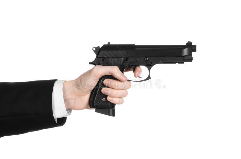 Armi da fuoco ed argomento di sicurezza: un uomo in un vestito nero che tiene una pistola su un fondo bianco isolato in studio fotografie stock libere da diritti