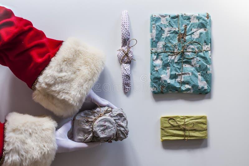 Armi del Babbo Natale che tengono parecchi regali fotografia stock