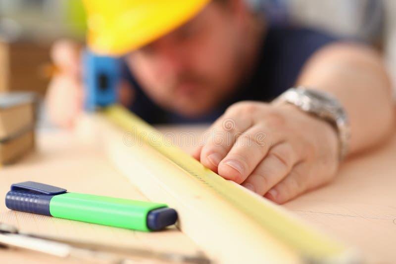Armi del lavoratore che misurano il primo piano di legno della barra fotografie stock libere da diritti