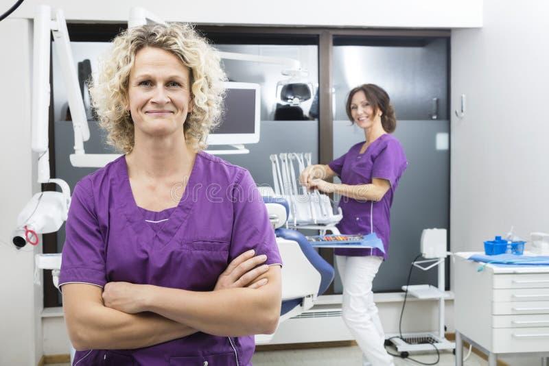 Armi di condizione dell'assistente attraversate con il collega che lavora in Dentis fotografia stock libera da diritti