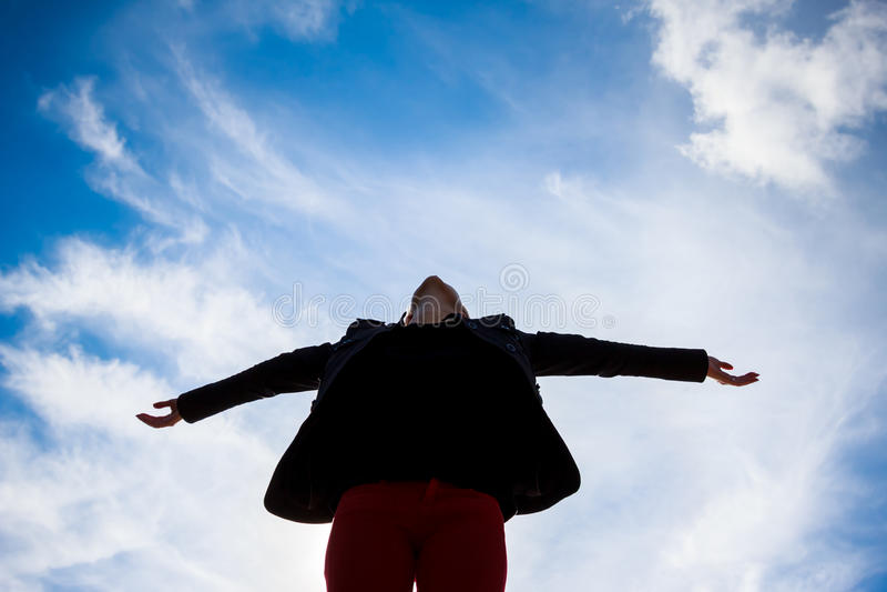 Armi di diffusione della giovane donna verso il cielo blu immagine stock libera da diritti