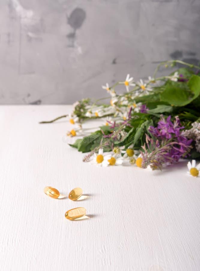 Armi di piante medicinali fresche sul tavolo e di pillole gialle fotografia stock libera da diritti