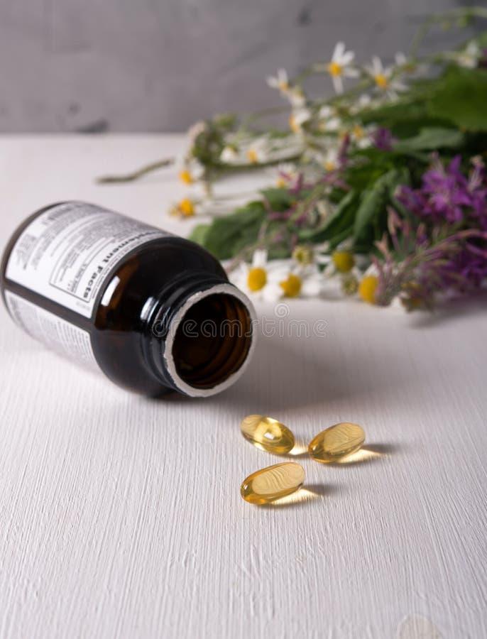 Armi di piante medicinali fresche sul tavolo e di pillole gialle immagini stock libere da diritti