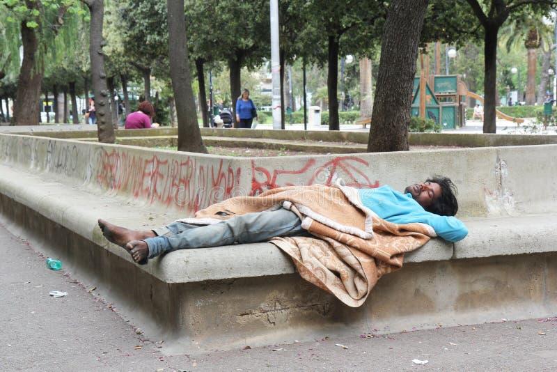 Armod homless man som sover på gatan royaltyfria bilder