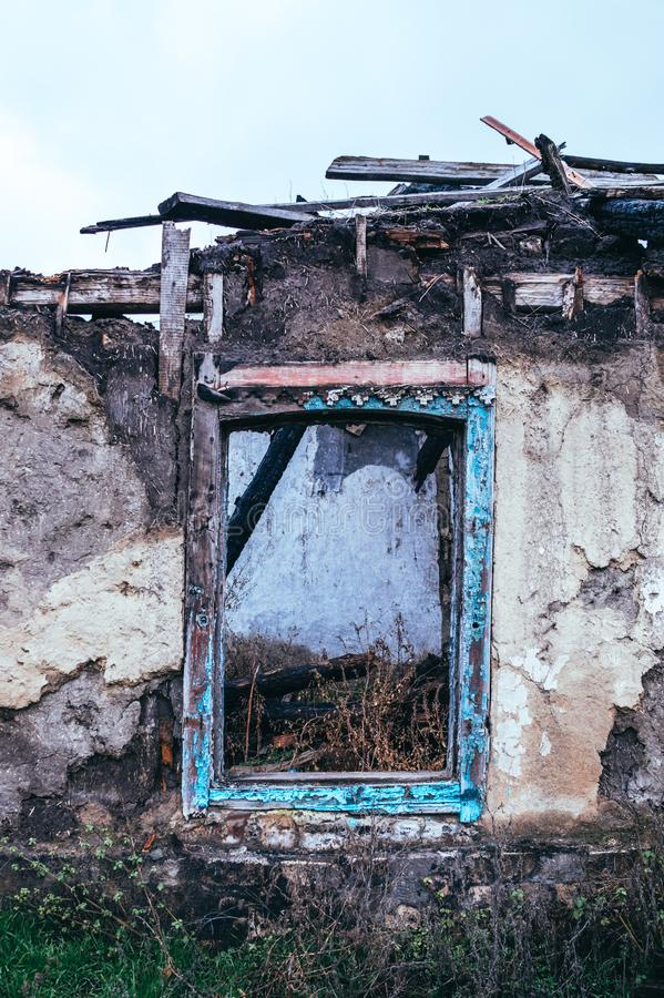 Armod och arbetslöshet Det gamla fönstret av det förstörda huset royaltyfria bilder