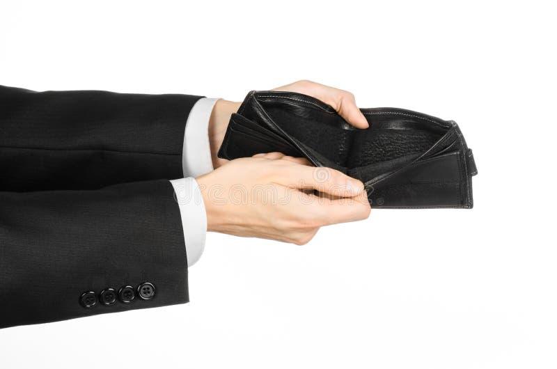 Armod och pengartema: en man i en svart dräkt som rymmer en tom handväska isolerad på vit bakgrund i studio royaltyfri fotografi