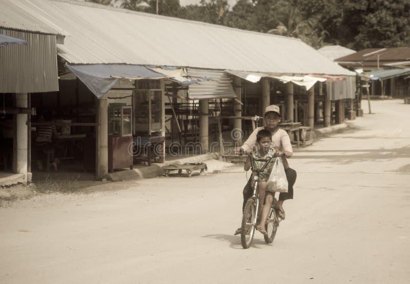 Armodpojkar som rider på en cykel längs en tom gata royaltyfria bilder