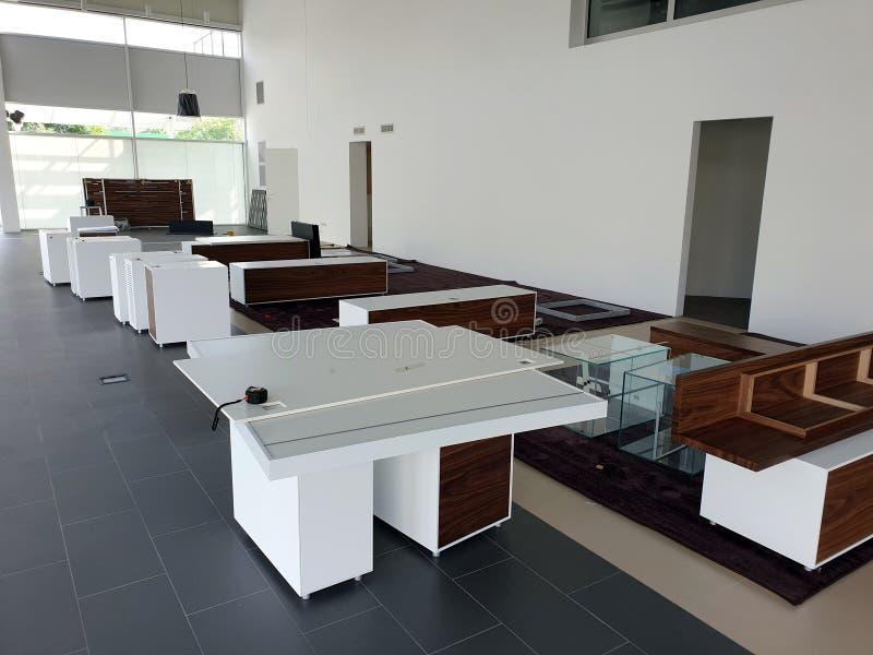 Armoires blanches avec les portes en bois sur le plancher dans la salle d'exposition Ensemble de meubles photos libres de droits